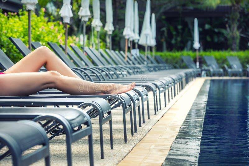 Vacanze estive nello stagno in una località di soggiorno Gambe della donna che si trovano e che si rilassano sugli sdrai fotografie stock