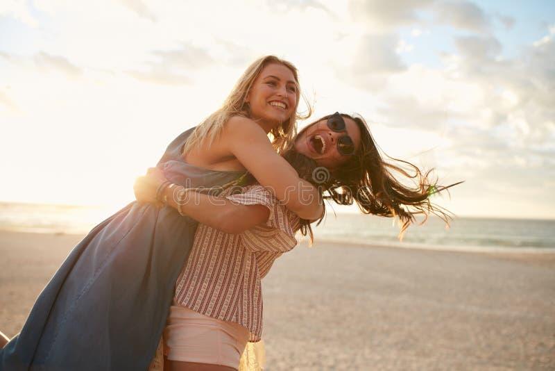 Vacanzieri delle giovani donne che godono sulla spiaggia immagine stock libera da diritti