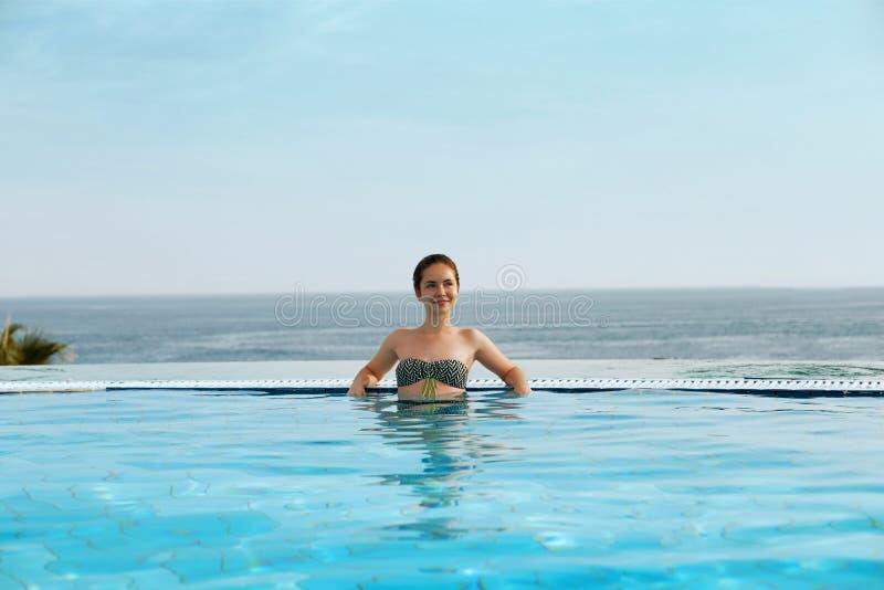 豪华旅游胜地 放松在无限游泳场水中的妇女 享受夏天旅行Vacatio的美好的愉快的健康女性模型 免版税库存照片