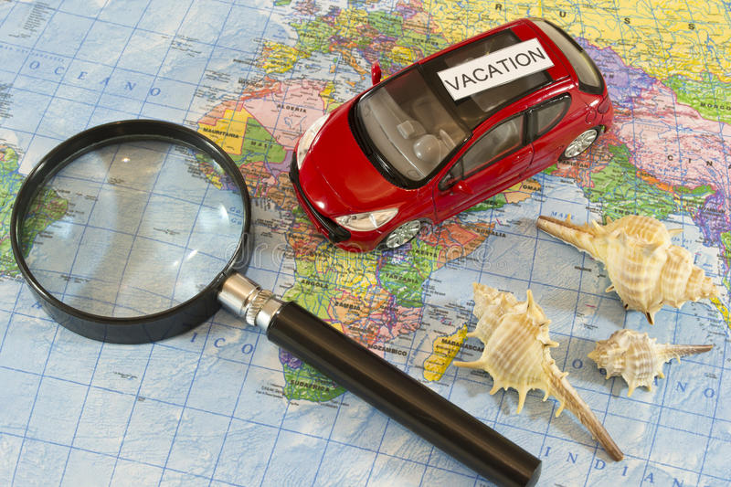 Vacation. Car, magnifying glass and shells over a map. Vacation and travel by car concept