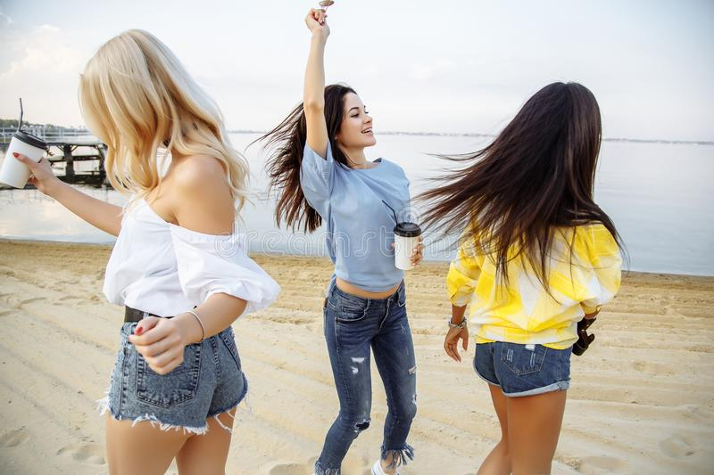 Vacation. Beach Party. Group of happy young women dancing at the beach on summer sunset.  royalty free stock image