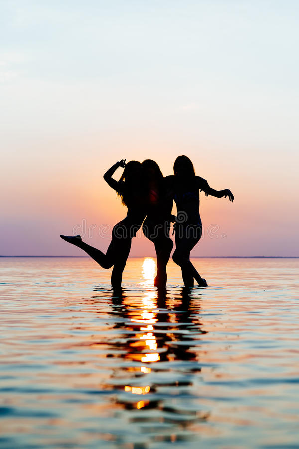 Vacation. Beach Party. Teenage girls having fun in water. Group of happy young people dancing at the on beautiful summer sunset. Silhouettes teen jumping stock photo