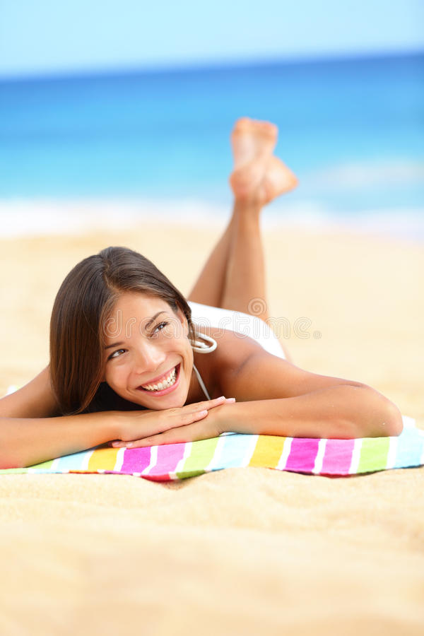 Vacation beach woman lying down relaxing looking. Vacation beach woman lying down relaxing and looking to the side and up. Happy smiling girl in bikini lying on stock image