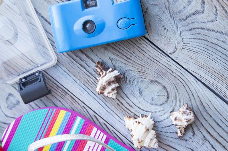 Vacation holiday concept. Vacation concept. Colorful slippers, camera with waterproof case and sea shells on a grey wooden background stock image