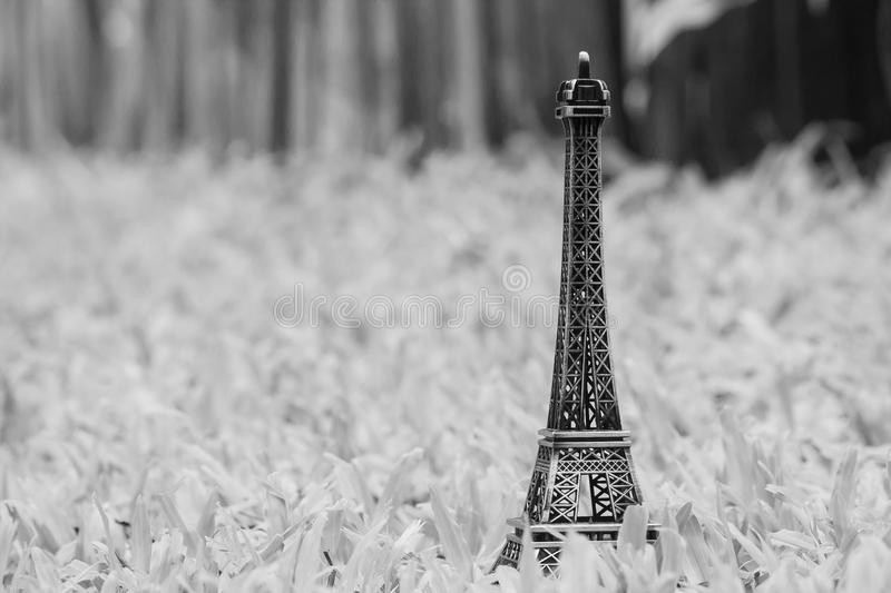 Vacation Concept : Little model of Eiffel tower on green grass in garden. Black and White filter effect royalty free stock photos