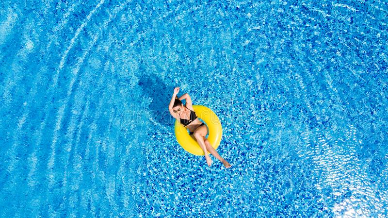 Vacation concept. Top view of slim young woman in bikini on the yellow air inflatable ring in the big swimming pool. stock photography