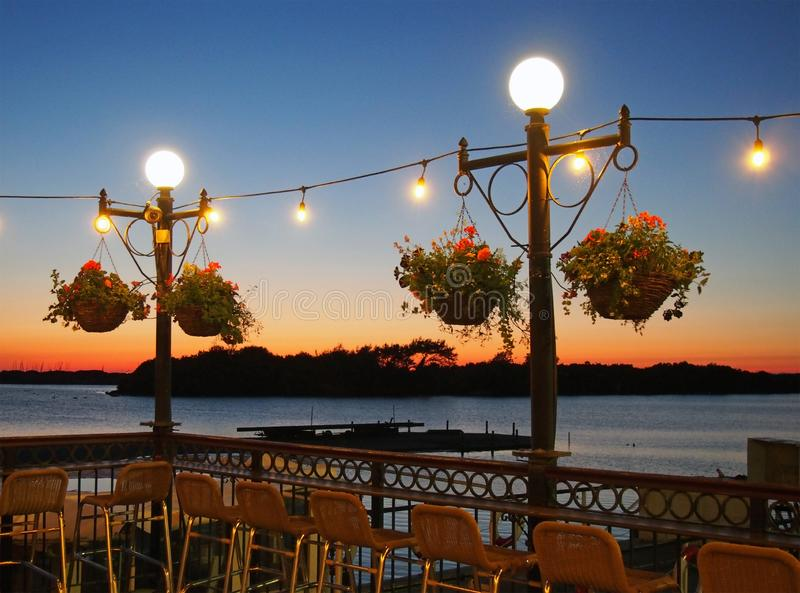 Vacation concept twilight scene with bar chairs around glowing lights at sunset over a lake with and island and jetty in royalty free stock photos