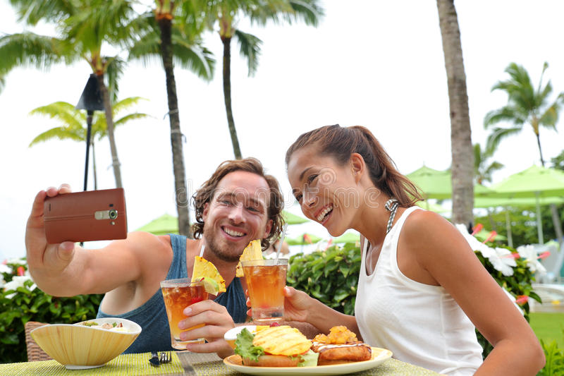 Vacation couple taking phone selfie at restaurant. Happy young interracial couple on summer holiday going out for dinner enjoying local food meal at outdoor stock photos