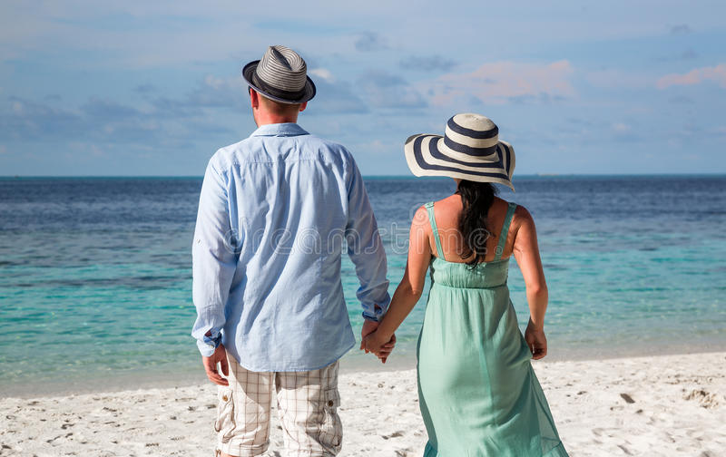 Vacation Couple walking on tropical beach Maldives. Couple on vacation walking on a tropical beach Maldives. Man and women romantic walk on the beach royalty free stock image
