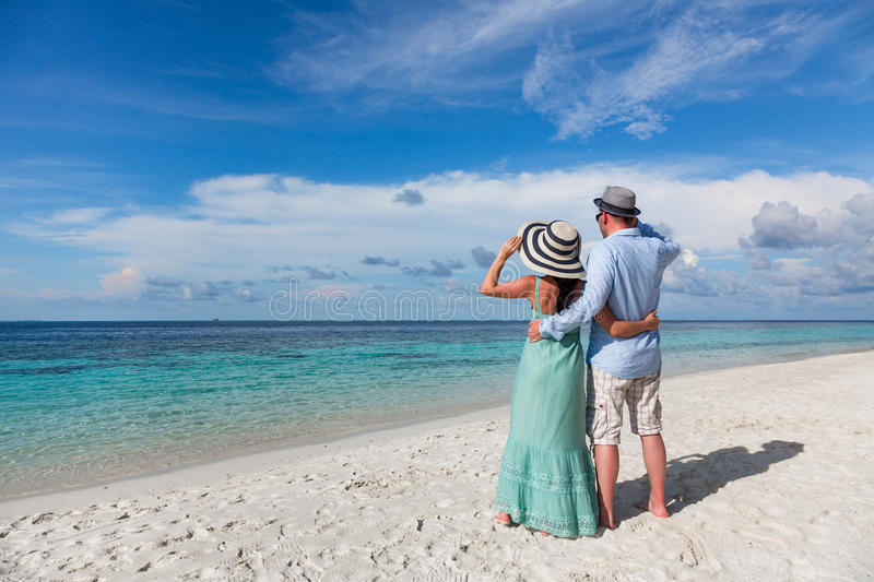 Vacation Couple walking on tropical beach Maldives. Couple on vacation walking on a tropical beach Maldives. Man and women romantic walk on the beach stock images
