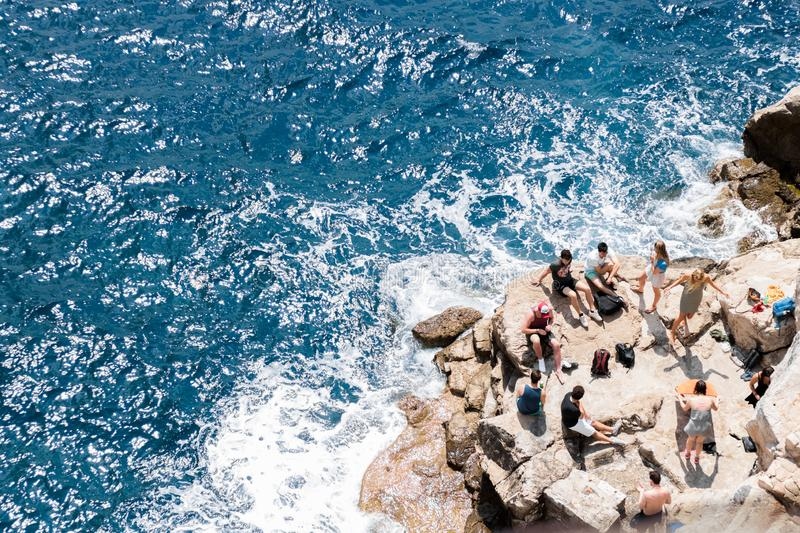Group of teenagers spending free time during summer  on rocky beach. royalty free stock images