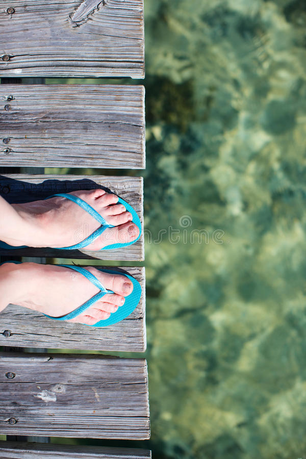 Vacation details. Woman legs wearing flip flops at wooden jetty by the sea royalty free stock photo