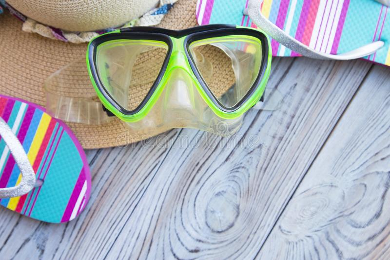 Vacation holiday concept. Vacation concept. Colorful slippers, swimming mask, straw hat on a grey wooden background, copy space royalty free stock photography