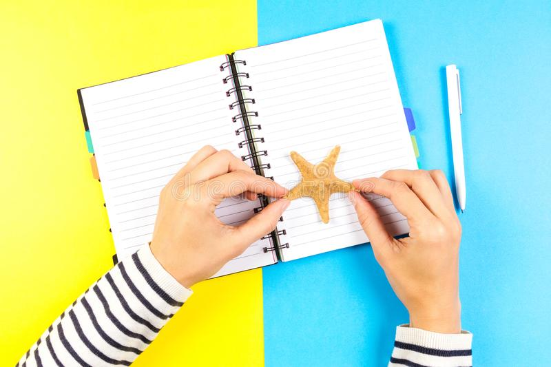 Woman hand holding starfish, pen and open notebook over blue and yellow background. stock photo