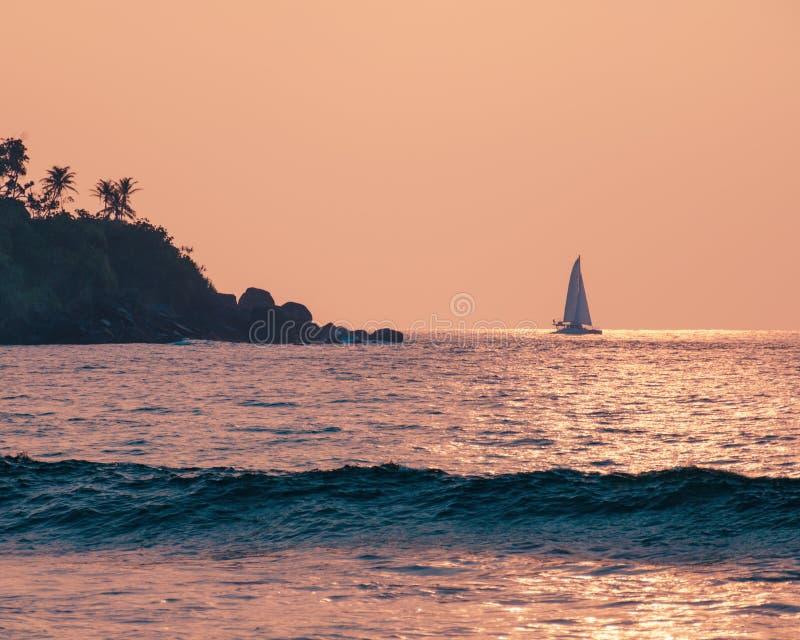 Vacation holidays postcard - beautiful landscape, sunset at warm sea, sailboat on horizon, island with palm tree. stock image