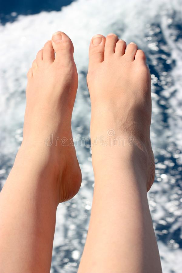 Vacation holidays. Women`s legs closeup on the background of sea water. Vertically framed shot royalty free stock image