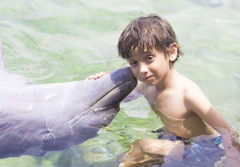 Vacation Lifestyle -Happy Boy hugging a dolphin stock photo