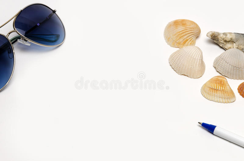 Vacation packing list sign. With sunglasses, seashells and pen on white background royalty free stock photos
