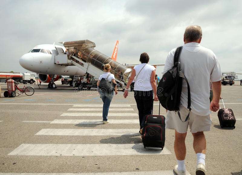 Vacation passengers. Holiday flight. Passengers boarding an Easyjet A319 jet at Pisa International Airport. Italy royalty free stock image
