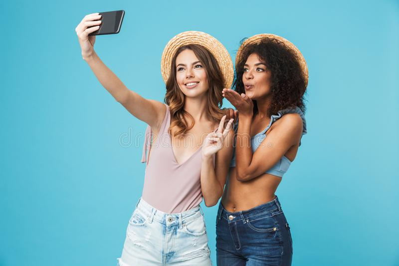 Vacation photo of two multiethnic girls wearing straw hats smiling and showing peace sign at camera, while taking selfie on smart royalty free stock image