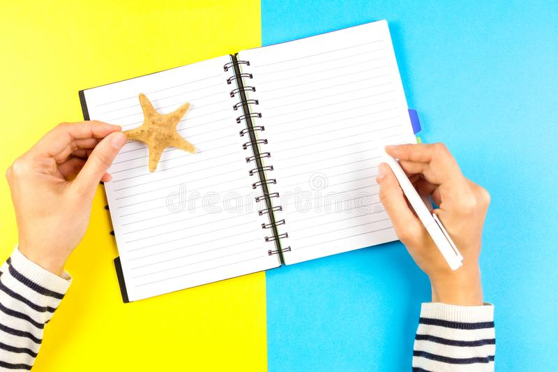Vacation planning concept. Woman hand writing in open travel notebook over blue and yellow background. royalty free stock photography