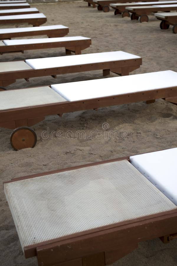 Vacation Relaxation Ideas. Empty Stretched Out Sunbed with White Cushion Lined Out in Rows. Adjustable Wood Recliner. With Wheel Stationed on a Fine Sand royalty free stock photo