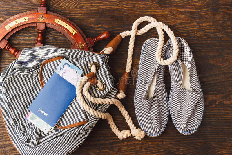 Vacation's items on the wooden background. Backpack, pair of espadrilles and passport with sea decorations on the wooden background stock photos
