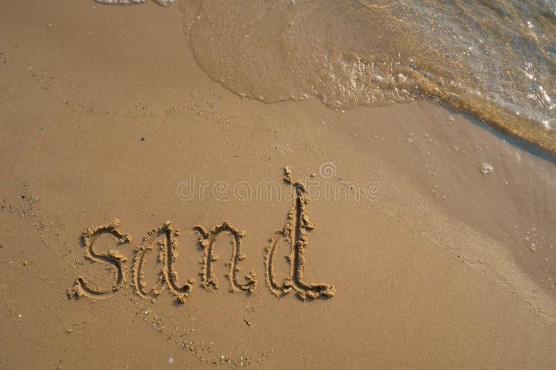 Vacation on the sand beach concept. Sand words written into the sand on the beach at Rayong, Thailand.  stock images