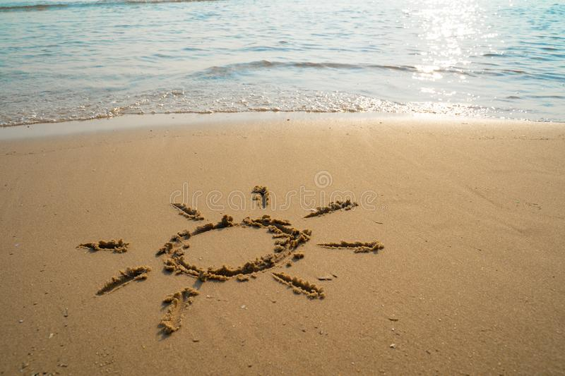 Vacation on the sand beach concept. The Sun symbol, sunshine drawing into the sand on the beach at Rayong, Thailand.  royalty free stock image