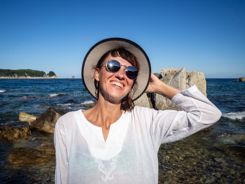 Vacation at sea: A girl in sunglasses and a straw on a rocky seashore in a bright sunny day. Bleak in the glasses. stock photos