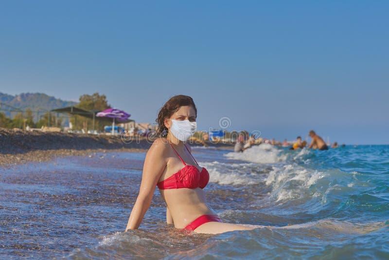 Vacation season 2020, woman at sea in face mask royalty free stock image