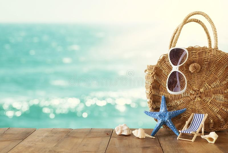 Vacation and summer concept with sea life style objects over wooden table infront of sea landscape background.  royalty free stock images