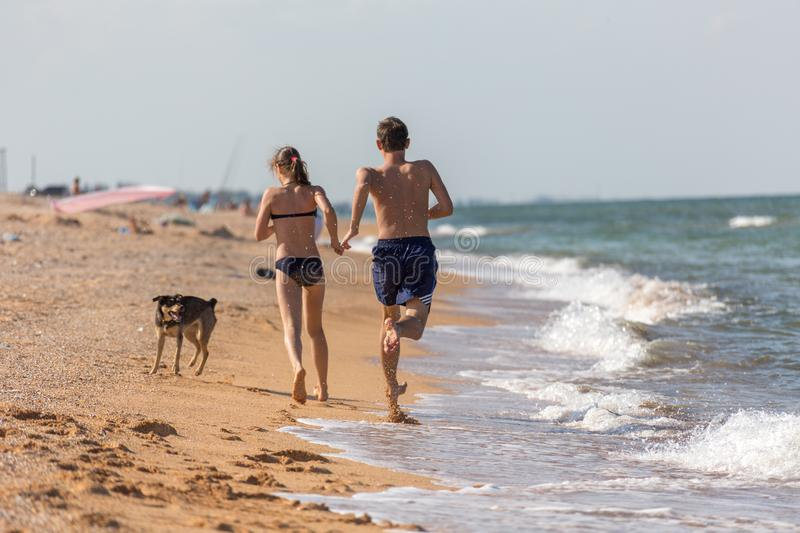 Vacation, summer day on the beach at the sea a couple of teenagers frolic and run on the wet sand stock image