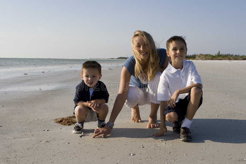 Vacation time. Mom with kids having fun on a beach. Ocean and sky in the background stock photos