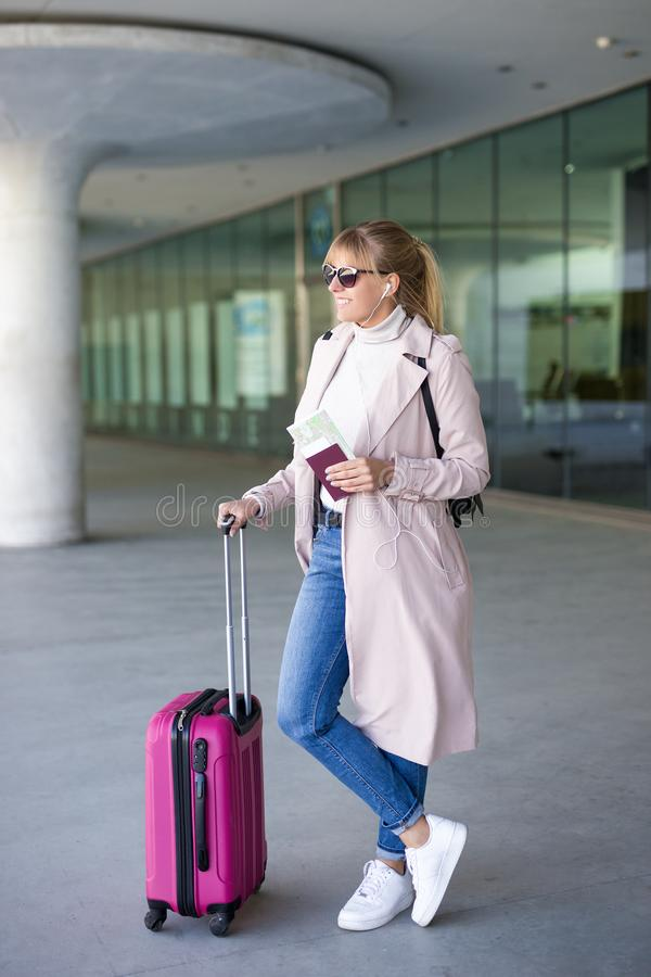 Vacation, tourism and travel concept - young woman tourist with suitcase and passport waiting boarding in airport or station royalty free stock image