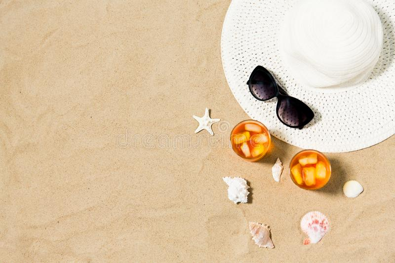 Cocktails, sun hat and sunglasses on beach sand royalty free stock photo