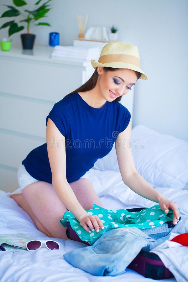 Vacation. Woman Who is Preparing for Rest. Young Beautiful Girl Sits on the Bed. Portrait of a Smiling Woman. Happy Girl royalty free stock photos