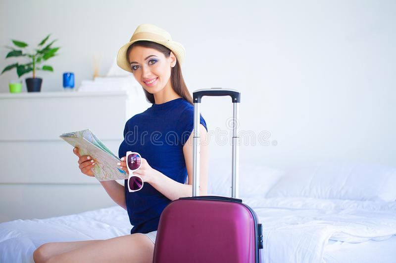 Vacation. Woman Who is Preparing for Rest. Young Beautiful Girl Sits on the Bed. Portrait of a Smiling Woman. Happy Girl stock photography