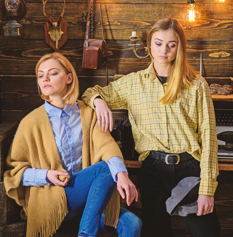 Vacation in woods concept. Girls on calm faces enjoy warm atmosphere while having rest. Friends or sisters spend. Pleasant evening in gamekeepers house royalty free stock photography