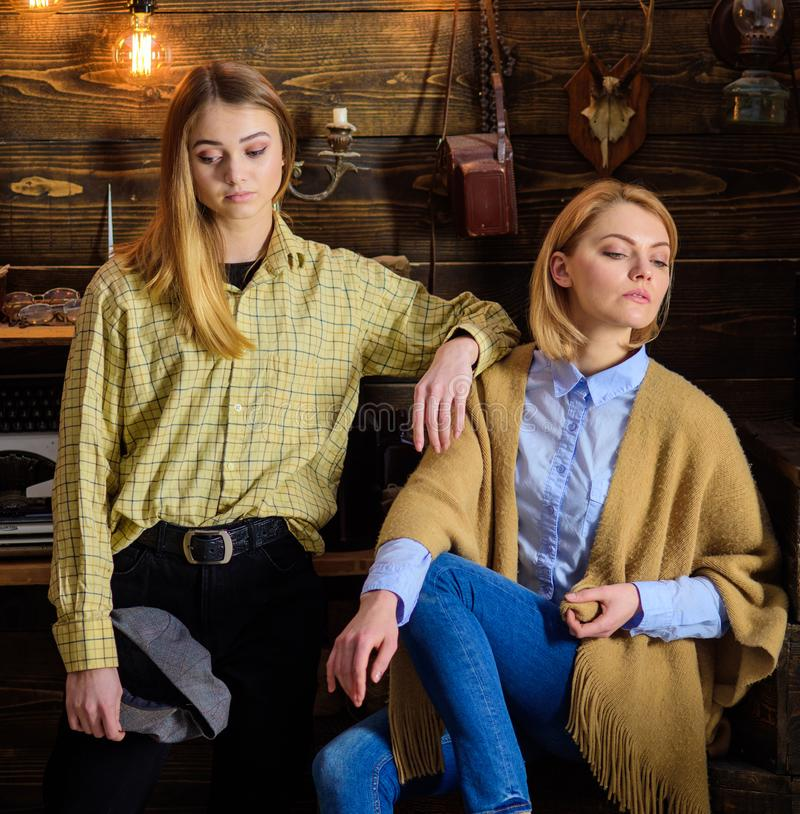 Vacation in woods concept. Girls on calm faces enjoy warm atmosphere while having rest. Friends or sisters spend. Pleasant evening in gamekeepers house stock photo