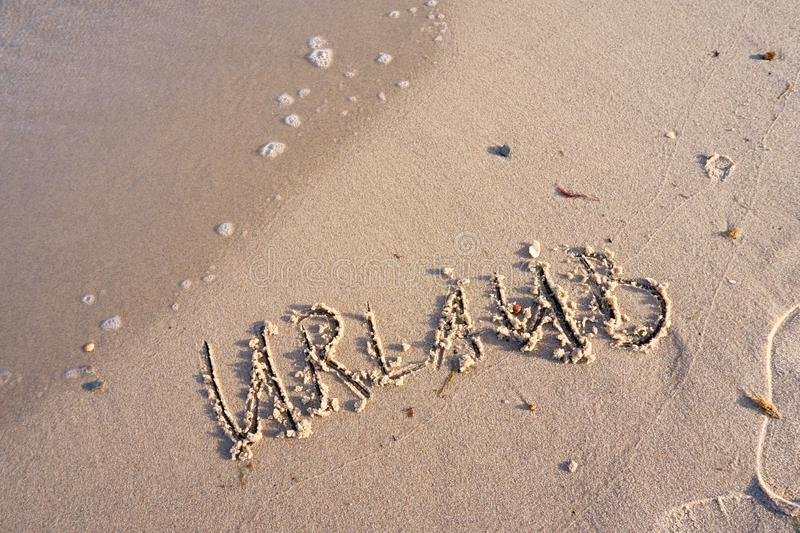 vacation word in beach sand stock photos