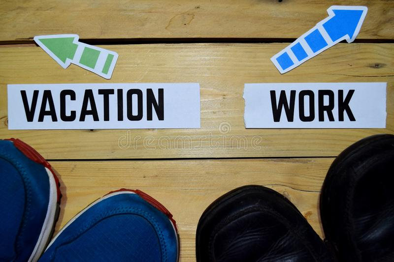Vacation or Work opposite direction signs with sneakers and boots on wooden. Vintage background. Business and education concepts stock images