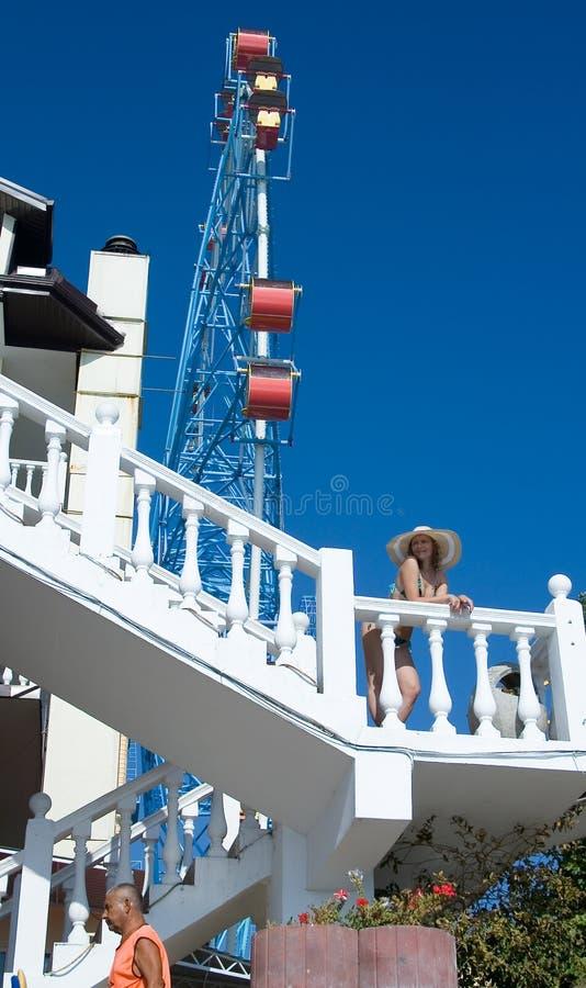 vacationers Ένα κορίτσι σε ένα μπικίνι και ένα καπέλο στέκεται στο σκαλοπάτι στοκ εικόνα