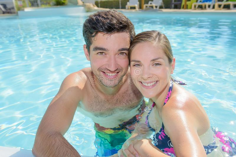 Vacationing couple in pool stock image