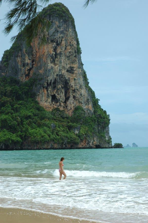 Vacationing Girl Wades into Shallow Surf. Krabi, Thailand. stock images