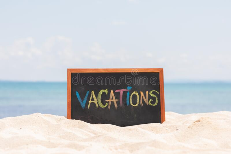 Vacations word in Blackboard on paradise tropical island beach with blue sky in summer for relaxation and vacations in Thailand royalty free stock image
