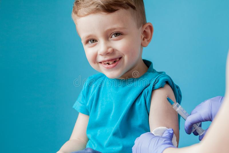 Vaccination concept. Female doctor vaccinating cute little boy on blue background, closeup.  royalty free stock photo