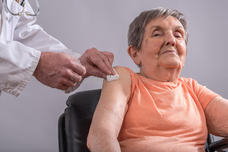 Vaccination of an elderly woman. Elderly woman getting the flu vaccine stock photography
