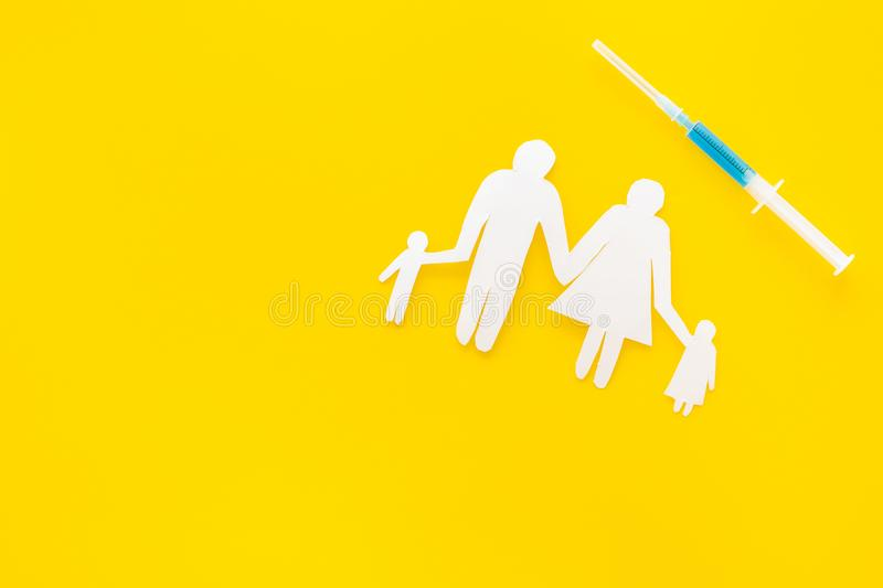 Vaccination for healthy family, vacctination of children. Flu. Syringe near family cutout on yellow background top view.  stock images