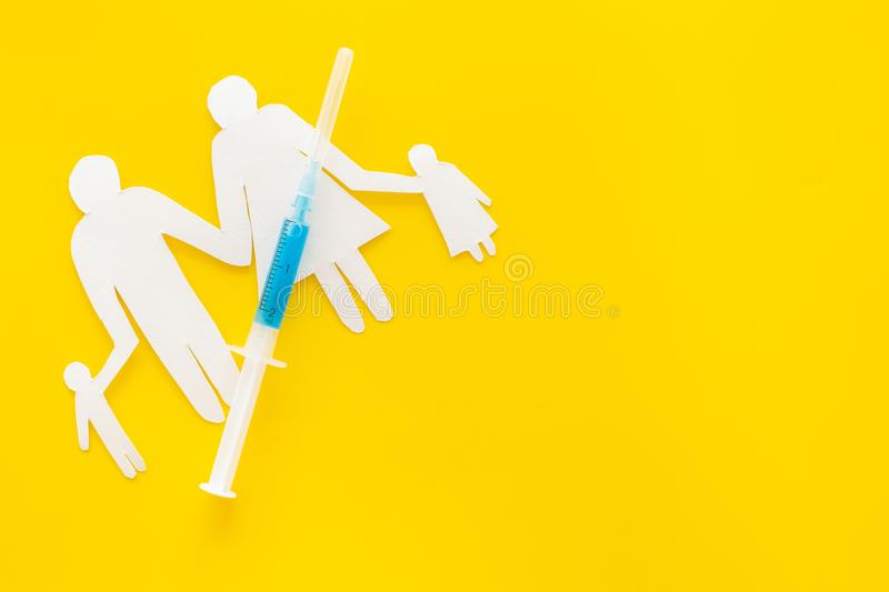 Vaccination for healthy family, vacctination of children. Flu. Syringe near family cutout on yellow background top view.  royalty free stock image